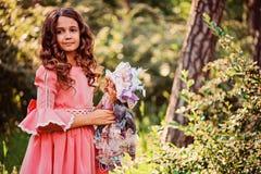 Sommerporträt des gelockten lächelnden Kindermädchens in Märchenprinzessinkleid mit Puppe im Wald Stockbilder