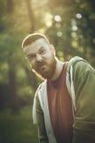 Sommerporträt des hübschen bärtigen Mannes, der lustiges Gesicht macht Stockfotos