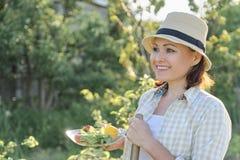 Sommerporträt im Freien der reifen positiven Frau im Strohhut auf Natur lizenzfreie stockfotos