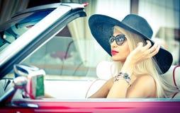 Sommerporträt im Freien der stilvollen blonden Weinlesefrau, die ein konvertierbares rotes Retro- Auto fährt Modernes attraktives Stockbilder