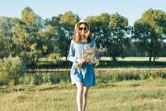 Sommerporträt im Freien des jugendlich Mädchens mit Blumenstrauß von Wildflowers, Strohhut Naturhintergrund, ländliche Landschaft lizenzfreie stockbilder