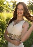Sommerporträt junger schöner Dame, die das lange weiße Abendkleid aufwirft im Park trägt Lizenzfreies Stockfoto