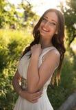 Sommerporträt junger schöner Dame, die das lange weiße Abendkleid aufwirft im Park trägt Lizenzfreies Stockbild