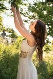 Sommerporträt junger schöner Dame, die das lange weiße Abendkleid aufwirft im Park trägt Lizenzfreie Stockbilder