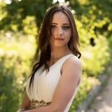 Sommerporträt junger schöner Dame, die das lange weiße Abendkleid aufwirft im Park trägt Lizenzfreie Stockfotos