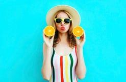 Sommerportr?tfrau, die in ihren H?nden zwei Scheiben orange Frucht im Strohhut auf buntem Blau h?lt lizenzfreie stockbilder