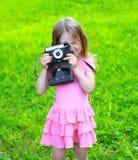 Sommerporträtkind mit der alten Retro- Weinlesekamera, die Spaß hat Lizenzfreie Stockfotografie