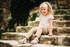 Sommerporträt des glücklichen Kindermädchens, das auf Steintreppe sitzt Lizenzfreie Stockfotos