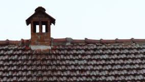 Sommerregen, der auf das rote Ziegeldach und den Kamin fällt stock video footage