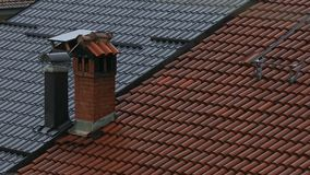 Sommerregen, der auf die roten Fliesen- und Metalldächer fällt stock video