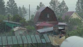 Sommerregen im Dorf, wolkiges Wetter, Regentropfen, die auf die Häuser fallen stock video