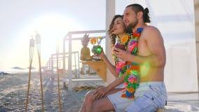 Sommerrest, Mädchen sein Freund zeigt Finger in Abstand auf tropischem Strand, hawaiische Leu auf jungen Leuten des Halses stock video footage