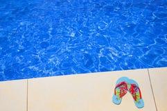 Sommerschuhe nahe dem Swimmingpool lizenzfreies stockbild
