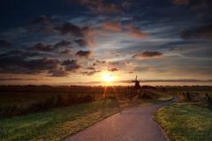 Sommersonnenaufgang über niederländischer Windmühle auf Ackerland Stockfoto