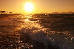 Sommersonnenuntergang auf Seestrand mit Welle Stockbilder