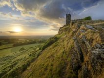 Sommersonnenuntergang ?ber Brentor, mit der Kirche von St. Michael de Rupe - St Michael des Felsens, am Rand des Dartmoor-Staatsa stockfotografie