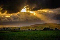 Sommersonnenuntergang mit Sonnenstrahlen durch Wolken Stockfotos