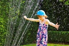 Sommerspaß mit Wasserberieselungsanlage stockfoto