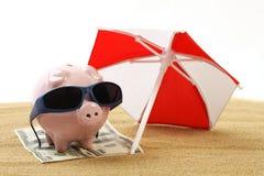 Sommersparschwein, das auf Tuch vom Dollar hundert Dollar mit Sonnenbrille auf dem Strandsand unter rotem und weißem Sonnenschutz Stockbilder