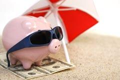 Sommersparschwein, das auf Tuch vom Dollar hundert Dollar mit Sonnenbrille auf dem Strandsand unter roten und weißen Sonnenschutz Stockfotografie