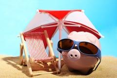 Sommersparschwein mit der Sonnenbrille, die auf Sand unter rotem und weißem Sonnenschutz nahe bei Strandstuhl steht Stockfotografie
