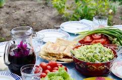 Sommerstillleben mit Tomaten, Wein, Brot, Salat und Zwiebel Lizenzfreies Stockbild
