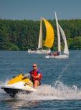 Sommerstimmung: gelbe und weiße Segel auf dem Hintergrund des blauen Himmels und einem Mann auf einem gelben Roller Stockfoto