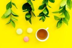 Sommerstimmung, Sommerteeparty Tasse Tee und Bonbons macarons nahe brignt Grün auf Draufsicht des gelben Hintergrundes Stockfoto