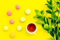 Sommerstimmung, Sommerteeparty Tasse Tee und Bonbons macarons nahe brignt Grün auf Draufsicht des gelben Hintergrundes Stockbilder