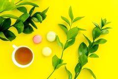 Sommerstimmung, Sommerteeparty Tasse Tee und Bonbons macarons nahe brignt Grün auf Draufsicht des gelben Hintergrundes Lizenzfreies Stockbild