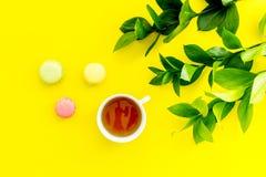 Sommerstimmung, Sommerteeparty Tasse Tee und Bonbons macarons nahe brignt Grün auf Draufsicht des gelben Hintergrundes Lizenzfreies Stockfoto
