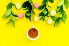 Sommerstimmung, Sommerteeparty Tasse Tee und Bonbons macarons nahe brignt Grün auf Draufsicht des gelben Hintergrundes kopieren Lizenzfreie Stockbilder
