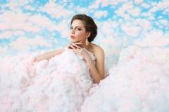 Sommerstimmungsbild wo schönes Mädchen, das unter den Wolken aufwirft Lizenzfreie Stockfotos