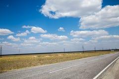 Sommerstraße unter Wolkenhimmel mit Freileitungsmasten auf dem Hintergrund Stockbild