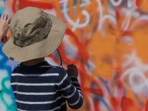 Sommerstraßen-Kunstjunge mit Farbenspray stockbilder