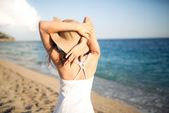 Sommerstrand-Modefrau, die Sommer genießen und Sonne, gehend der Strand nahe dem klaren blauen Meer und setzen ihre Hände hinter  Stockfotografie