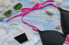 Sommerstrand-Seekonzept Blauer hölzerner Hintergrund mit unterschiedlichem Zubehör, Oberteile, Starfish, Sonnenbrille, swimsuite Stockbilder