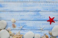 Sommerstrand-Seekonzept Blauer hölzerner Hintergrund mit verschiedenen Oberteilen, weißen Steinen und Sand Rote sratfish in der M Lizenzfreies Stockfoto