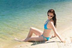 Sommerstrandfrau im Bikini, der auf Küste sitzt lizenzfreie stockfotografie