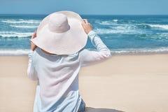 Sommerstrandkonzept Frau im Großen Hut auf idyllischem Strand Weißer Sand, blauer Himmel und Kristallmeer lizenzfreie stockfotos