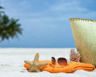 Sommerstrandtasche mit Koralle, Tuch und Flipflops auf sandigem Strand Stockbild