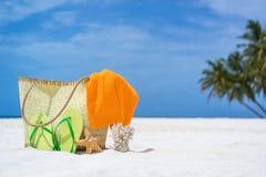 Sommerstrandtasche mit Koralle, Tuch und Flipflops auf sandigem Strand Lizenzfreie Stockfotos