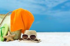 Sommerstrandtasche mit Starfish, Tuch, Sonnenbrille und Flipflops auf sandigem Strand stockbilder