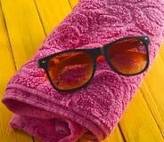 Sommerstrandzubehör auf einem gelben Holztisch Tuch, Sonnenbrille Das Konzept eines Erholungsortes auf dem Strand Stockbilder