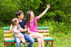Sommerszene der glücklichen jungen Familie, die selfies mit ihrem Smartphone im Park nimmt Stockbild