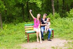 Sommerszene der glücklichen jungen Familie, die selfies mit ihrem Smartphone im Park nimmt Stockbilder