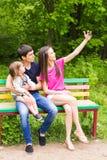 Sommerszene der glücklichen jungen Familie, die selfies mit ihrem Smartphone im Park nimmt Lizenzfreie Stockfotos
