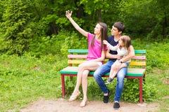Sommerszene der glücklichen jungen Familie, die selfies mit ihrem Smartphone im Park nimmt stockfotos