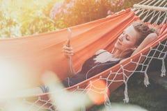 Sommertag, junge Frau, die in der orange Hängematte im Park liegt und Musik auf Smartphone hört Lizenzfreie Stockbilder