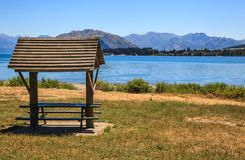 Sommertagesansicht von Schattenschutz für Touristen am See Wanaka, Neuseeland mit blauem See- und Gebirgshintergrund Stockfotos